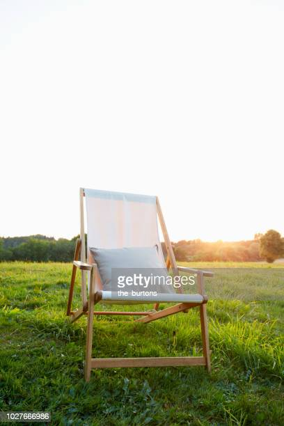 deck chair with pillow on meadow at sunset - chaise longue photos et images de collection