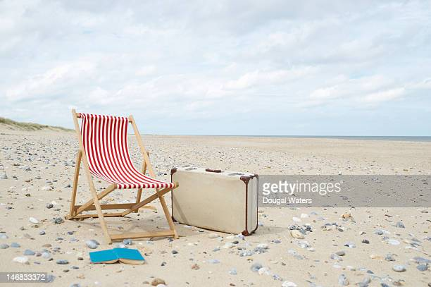 Deck chair with suitcase and book at beach.