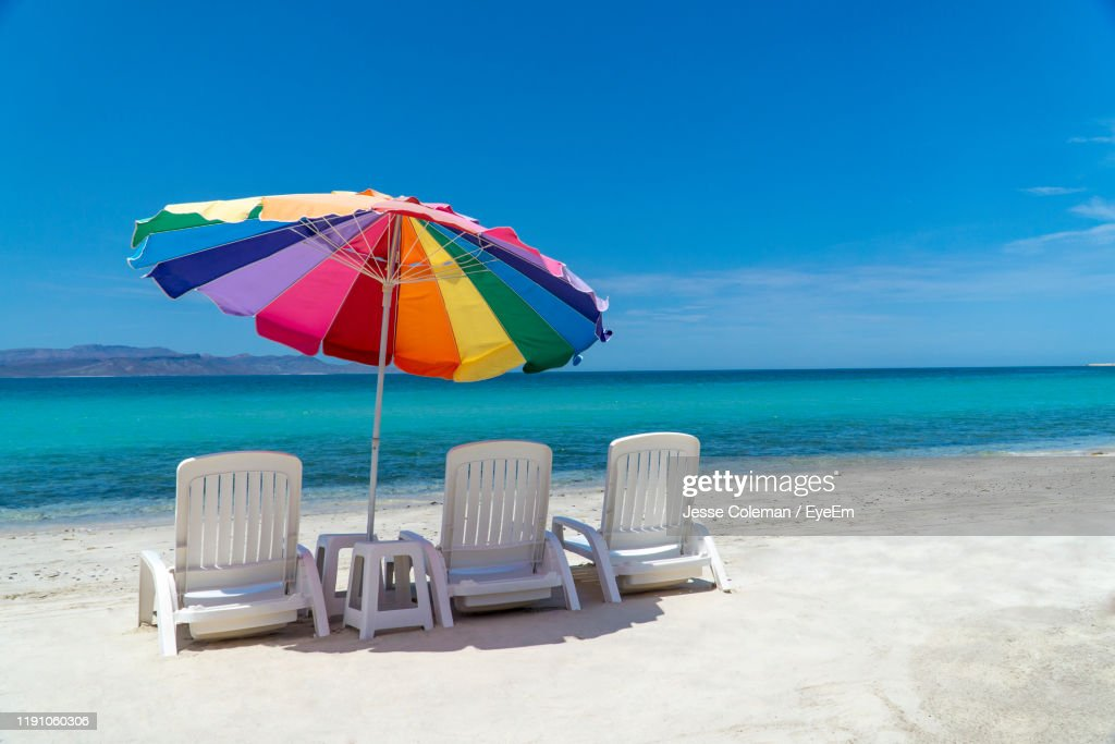 Deck Chairs And Parasol At Beach Against Blue Sky : Stock Photo
