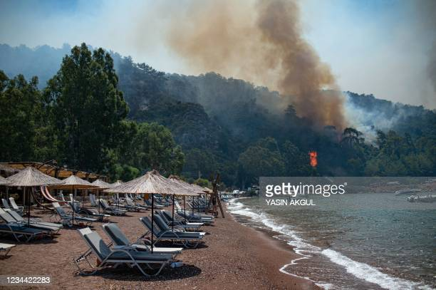 Deck chairs are seen on a beach in front of smoke and flames rising from a forest fire on August 3, 2021 in Mugla, a Marmaris' district, as Turkey...