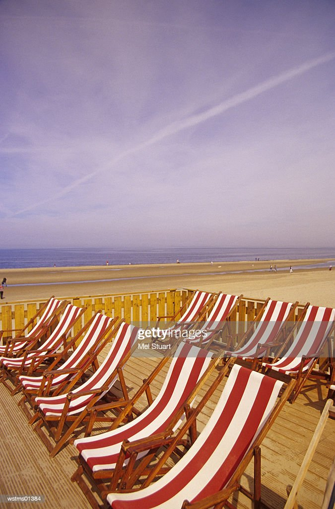 Deck chairs in a line on sandy beach, North Sea, Holland : Stock Photo