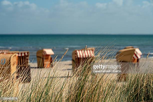 deck chairs on beach against sky - fehmarn stock-fotos und bilder