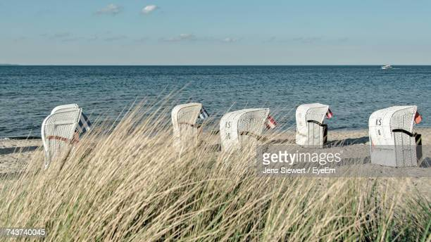 deck chairs on beach against sky - schleswig holstein stock photos and pictures