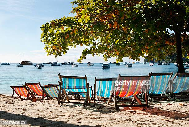 deck chairs on beach, boats in bay - travel14 stock pictures, royalty-free photos & images
