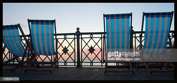 deck chairs on hastings pier - hastings stock photos and pictures