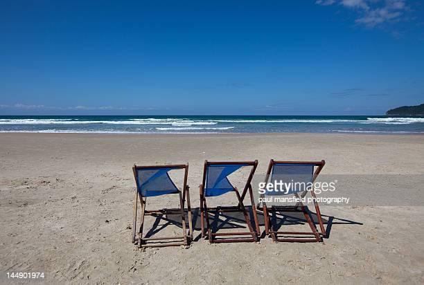 Deck chairs on sandy beach