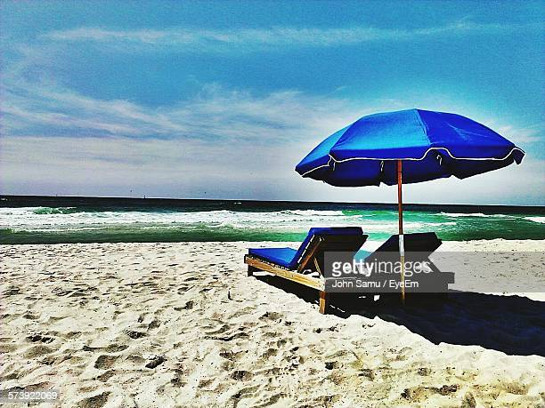 Deck Chairs With Parasol On Beach Against Sky
