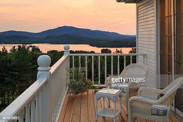deck overlooking lake at sunset - moosehead lake stock photos and pictures