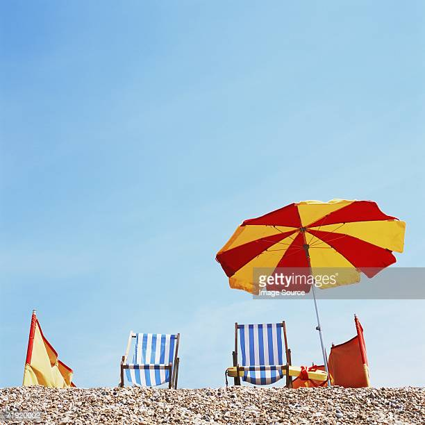 deckchairs and parasol on the beach - windbreak stock pictures, royalty-free photos & images