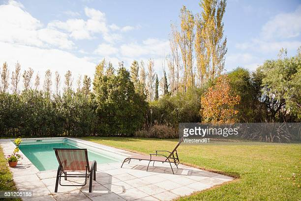 Deckchairs at poolside in garden