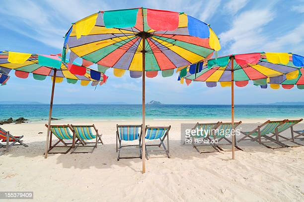 Deckchairs on a beach under parasols