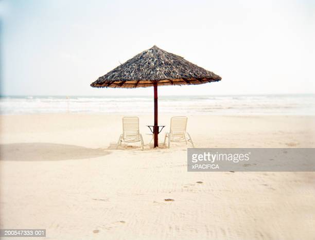 Deckchairs with bamboo thatch umbrella on beach