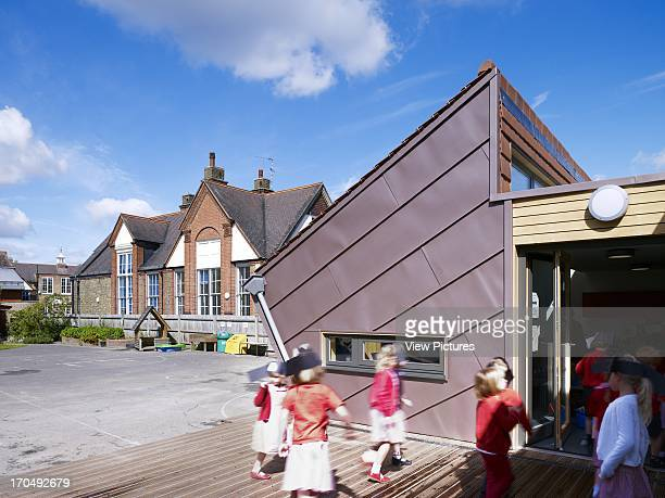 Decking view of extension school children playing Dulwich Village Infant School London United Kingdom Architect Cazenove Architects 2012