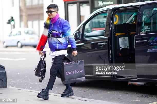 Declan Chan wears a multicolor scarf a blue bomber jacket with a printed car logo cropped pants black sneakers a black bag outside John Lawrence...