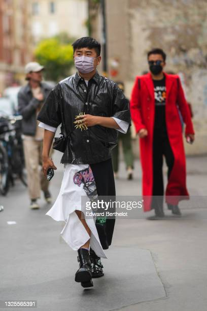 Declan Chan wears a white t-shirt, a black oversized shiny vinyl short sleeves shirt, gold nailed / studded finger rings, a black shiny leather...
