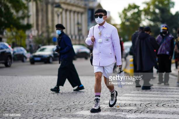 Declan Chan wears sunglasses, a white face mask, a necklace, a pale pink padded jacket, a Chanel Airpods case, white shorts, socks, white boots, a...
