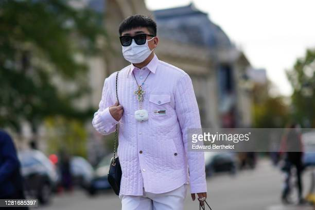 Declan Chan wears sunglasses, a white face mask, a necklace, a pale pink padded jacket, a Chanel Airpods case, white shorts, outside Chanel, during...