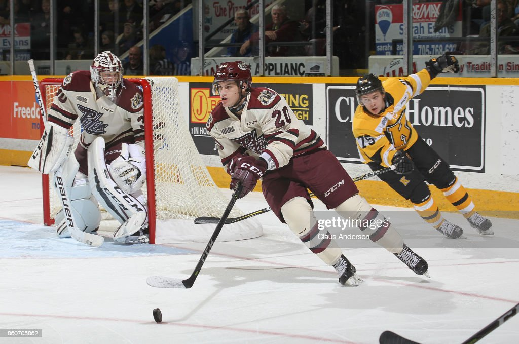 Declan Chisholm #20 of the Peterborough Petes skates away from a checking Linus Nyman #75 of the Kingston Frontenacs in an OHL game at the Peterborough Memorial Centre on October 12, 2017 in Peterborough, Ontario.