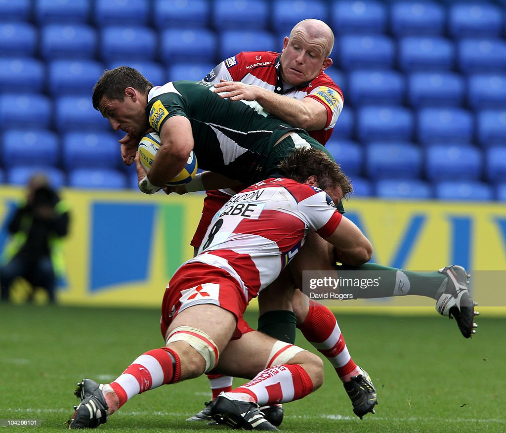Declan Danagher of London Irish is tackled by Scott Lawson and Brett Deacon during the Aviva Premiership match between London Irish and Gloucester at the Madejski Stadium on September 19, 2010 in Reading, England.