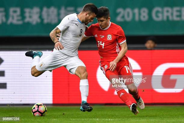 Declan John right of Wales national football team challenges Nahitan Nandez of Uruguay national football team in their final match during the 2018...