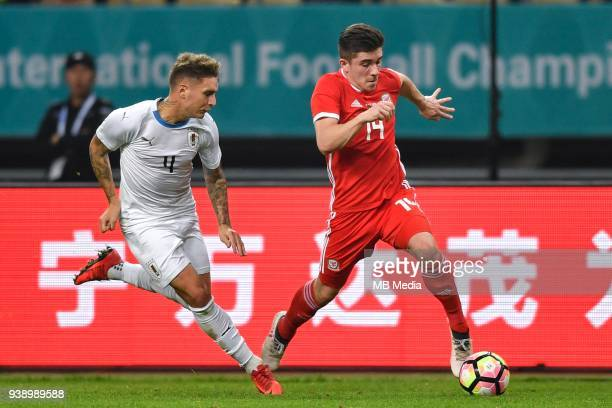 Declan John right of Wales national football team kicks the ball to make a pass against Guillermo Varela of Uruguay national football team in their...