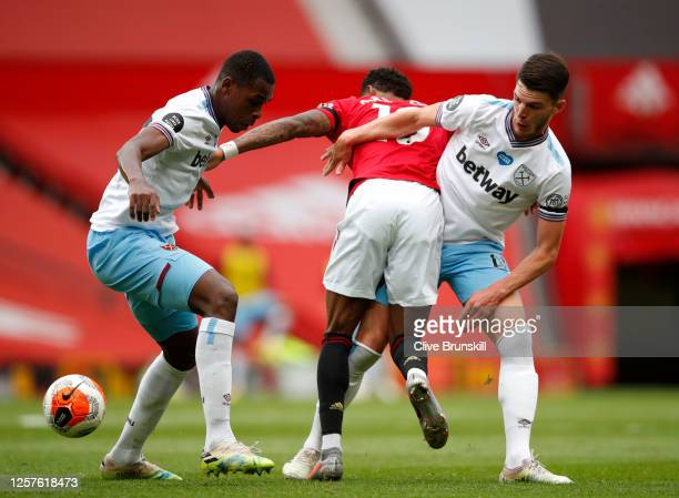 Declan Rice and Issa Diop of West Ham United battle for possession with Marcus Rashford of Manchester United during the Premier League match between...