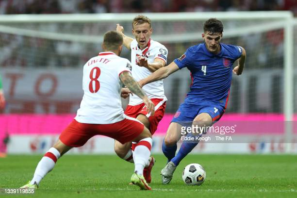 Declan Rice of England is challenged by Adam Buksa during the 2022 FIFA World Cup Qualifier match between Poland and England at Stadion Narodowy on...
