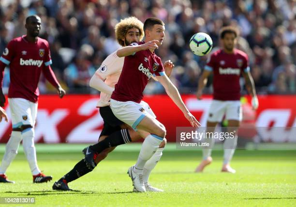 Declan Rice of West Ham United competes for the ball with Marouane Fellaini of Manchester United during the Premier League match between West Ham...