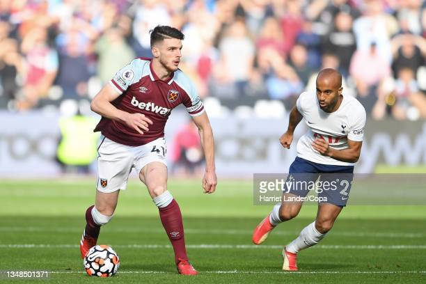 Declan Rice of West Ham United runs with the ball under pressure from Lucas Moura of Tottenham Hotspur during the Premier League match between West...