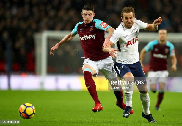 Declan Rice of West Ham United runs with the ball under pressure from Harry Kane of Tottenham Hotspur during the Premier League match between...