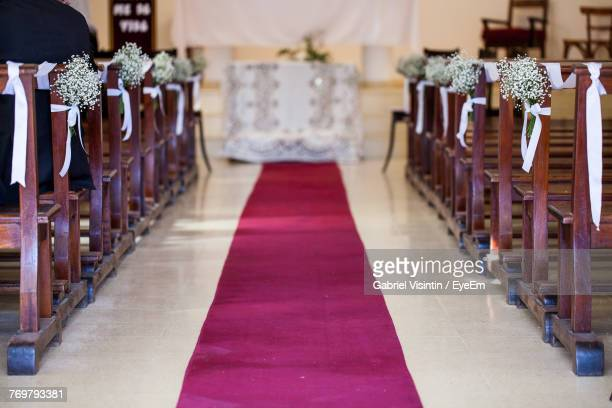 decorated benches and carpet in church - church wedding decorations stock pictures, royalty-free photos & images
