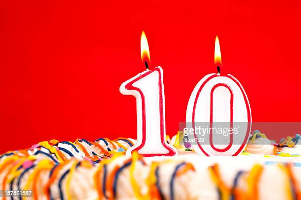 Decorated birthday cake with number 10 candles.  Red background