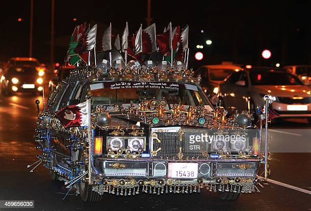 A decorated car flying the national flag of Qatar drives near a bus carrying members of the national football team during celebrations in Doha on...