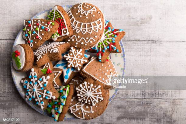 decorated christmas gingerbread cookies in a plate - christmas cookies stock pictures, royalty-free photos & images