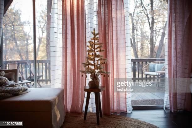 decorated christmas tree in living room, verandah in background - heshphoto photos et images de collection