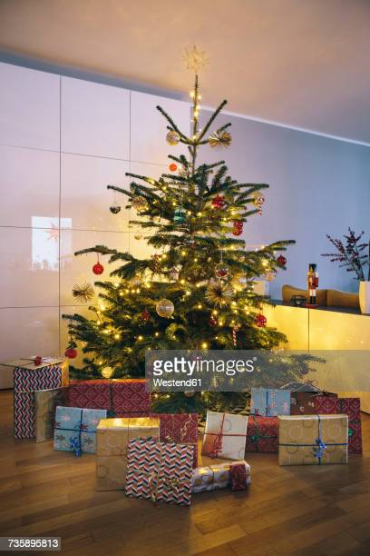 Decorated Christmas tree in living room with Christmas presents in the foreground