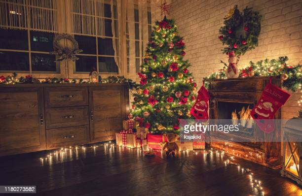 decorated christmas tree near fireplace at home - christmas tree stock pictures, royalty-free photos & images