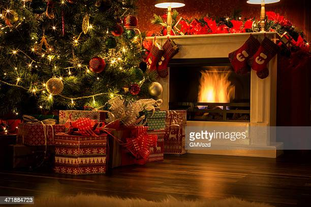 decorated christmas tree with presents and fireplace - christmas tree stock pictures, royalty-free photos & images
