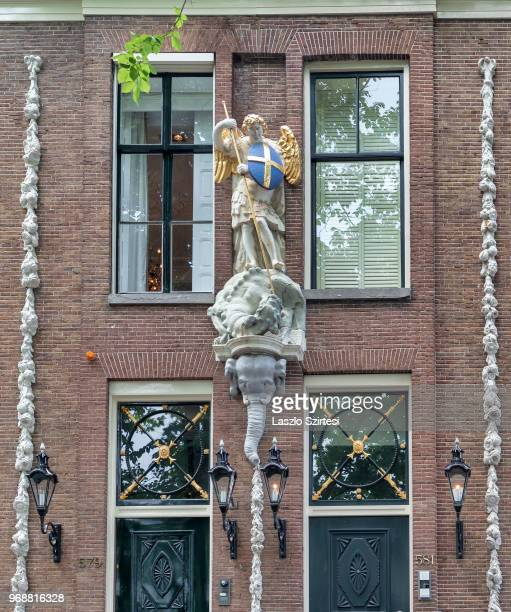 Decorated facade is seen from the Herengracht Canal on May 30 2018 in Amsterdam Netherlands The sculpture illustrates Saint George and the Dragon
