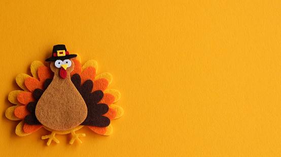 decorated felt turkey on an orange festive background with writing space 1185905137