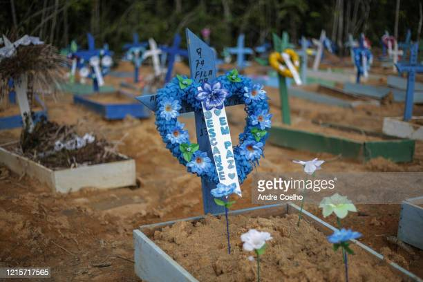 """Decorated sign with the inscription that reads """"Rest in peace"""" is seen over a grave of a coronavirus victim the Parque Tarumã cemetery on May 27,..."""