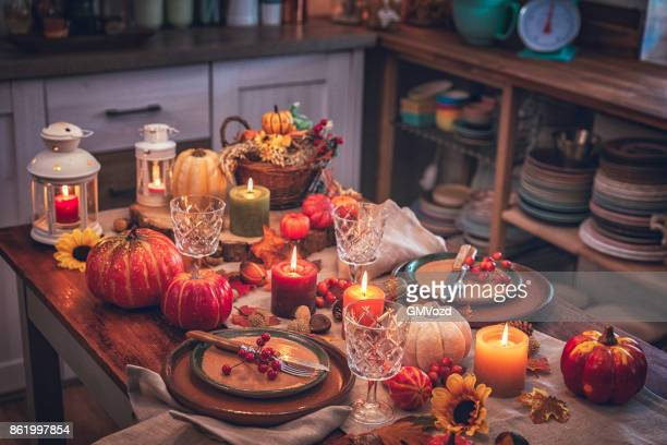 decorated table for thanksgiving dinner with candles, pumpkins, leafs and nuts - thanksgiving background stock photos and pictures