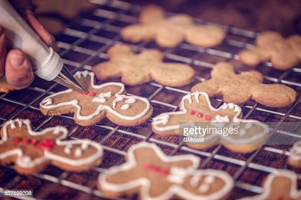 decorating christmas cookies with icing - gingerbread man stock photos and pictures