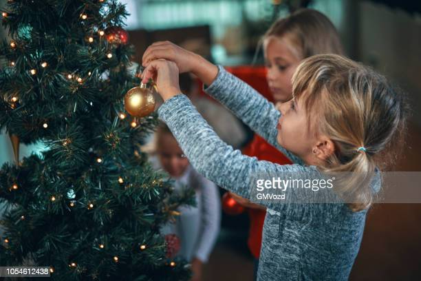 decorating christmas tree with ornaments and christmas lights - tradition stock pictures, royalty-free photos & images