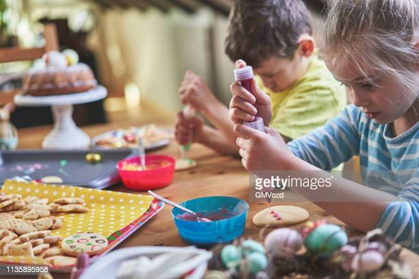 decorating easter cookies with colorful icing - easter cake stock pictures, royalty-free photos & images