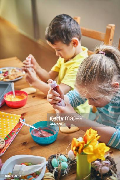 decorating easter cookies with icing for easter time - easter cake stock pictures, royalty-free photos & images