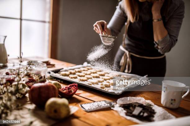 decorating gingerbread cookies with powdered sugar - icing sugar stock pictures, royalty-free photos & images