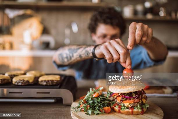 decorating tasty hamburgers - burger stock pictures, royalty-free photos & images