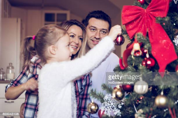 Decorating the Christmas tree. Blonde mother, father and cute girl having fun with Christmas decoration in their home. Belgrade, Serbia, Europe