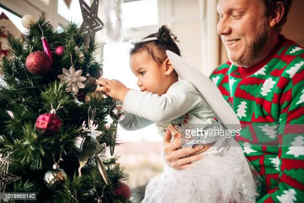 decorating the christmas tree with her father - estrelas de natal imagens e fotografias de stock
